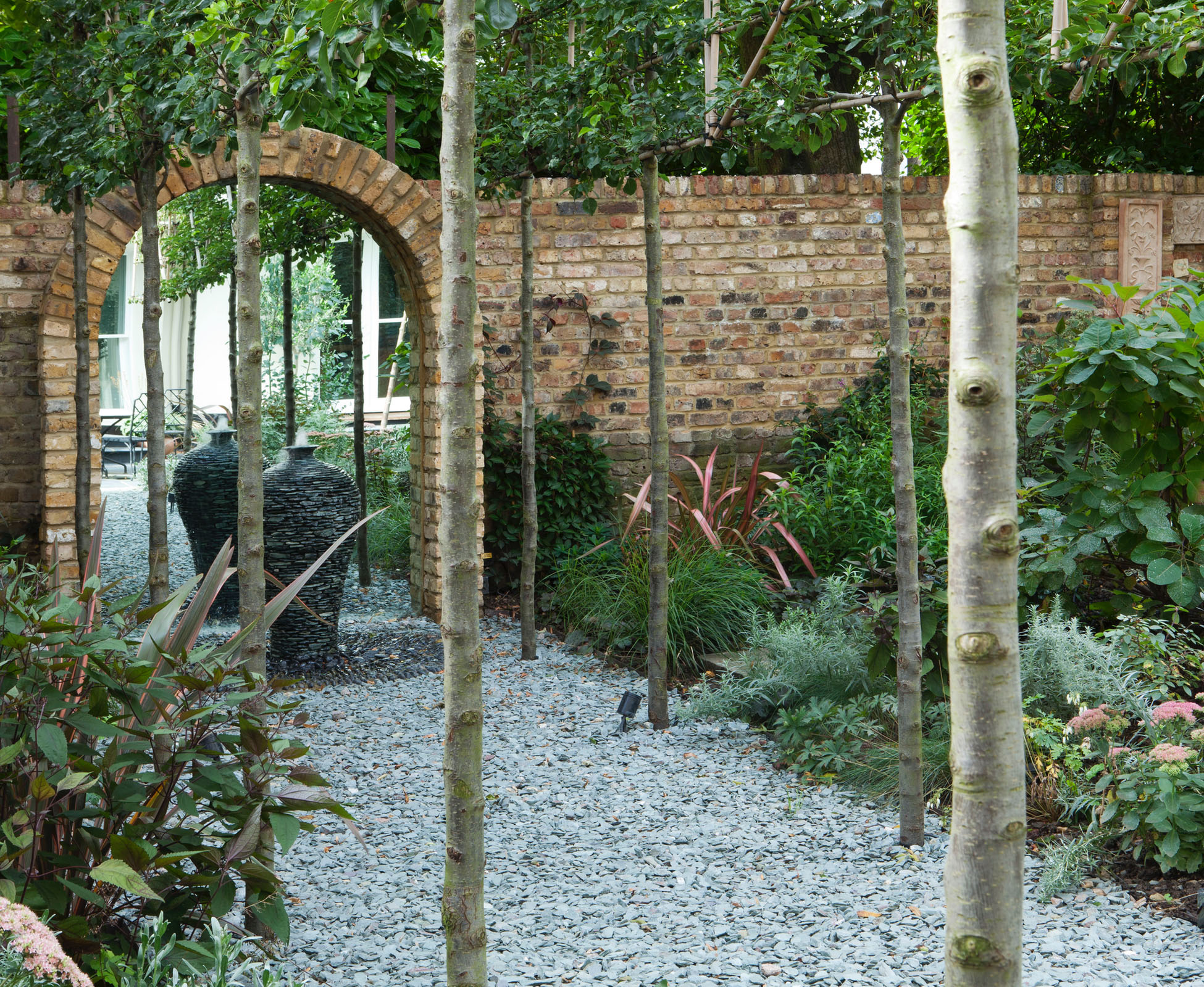 An avenue of pleached Pyrus, leads you to the mirrored arch and water feature.