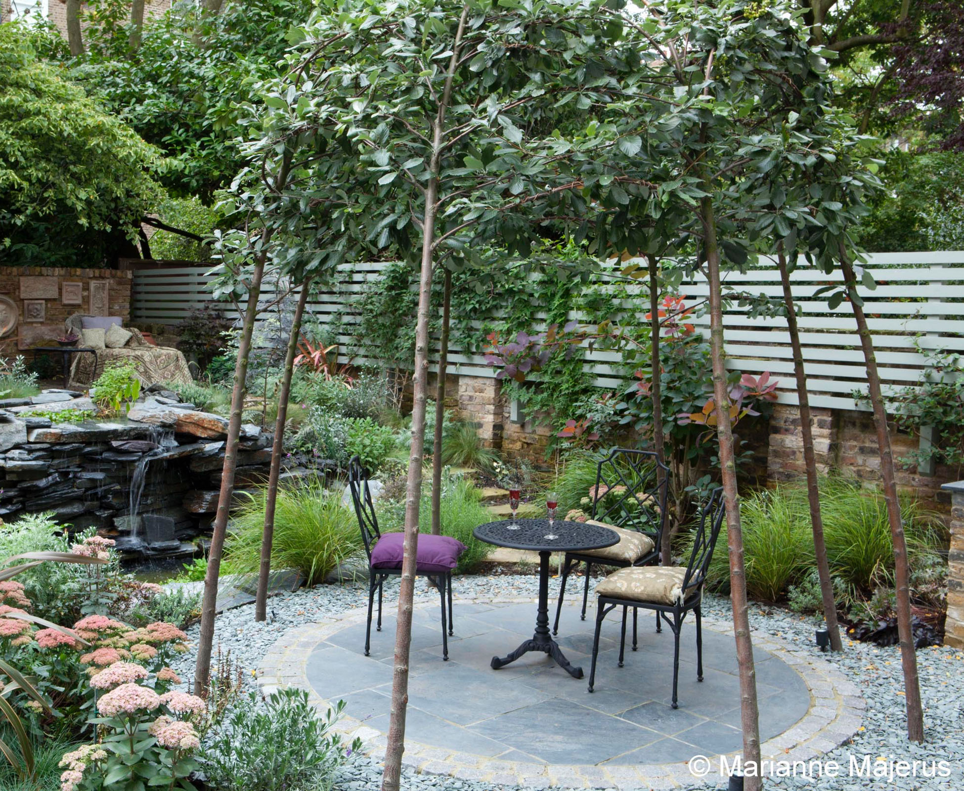 The trees have been trained to create a unusual canopy for the slate patio, that sits in front of the water feature.