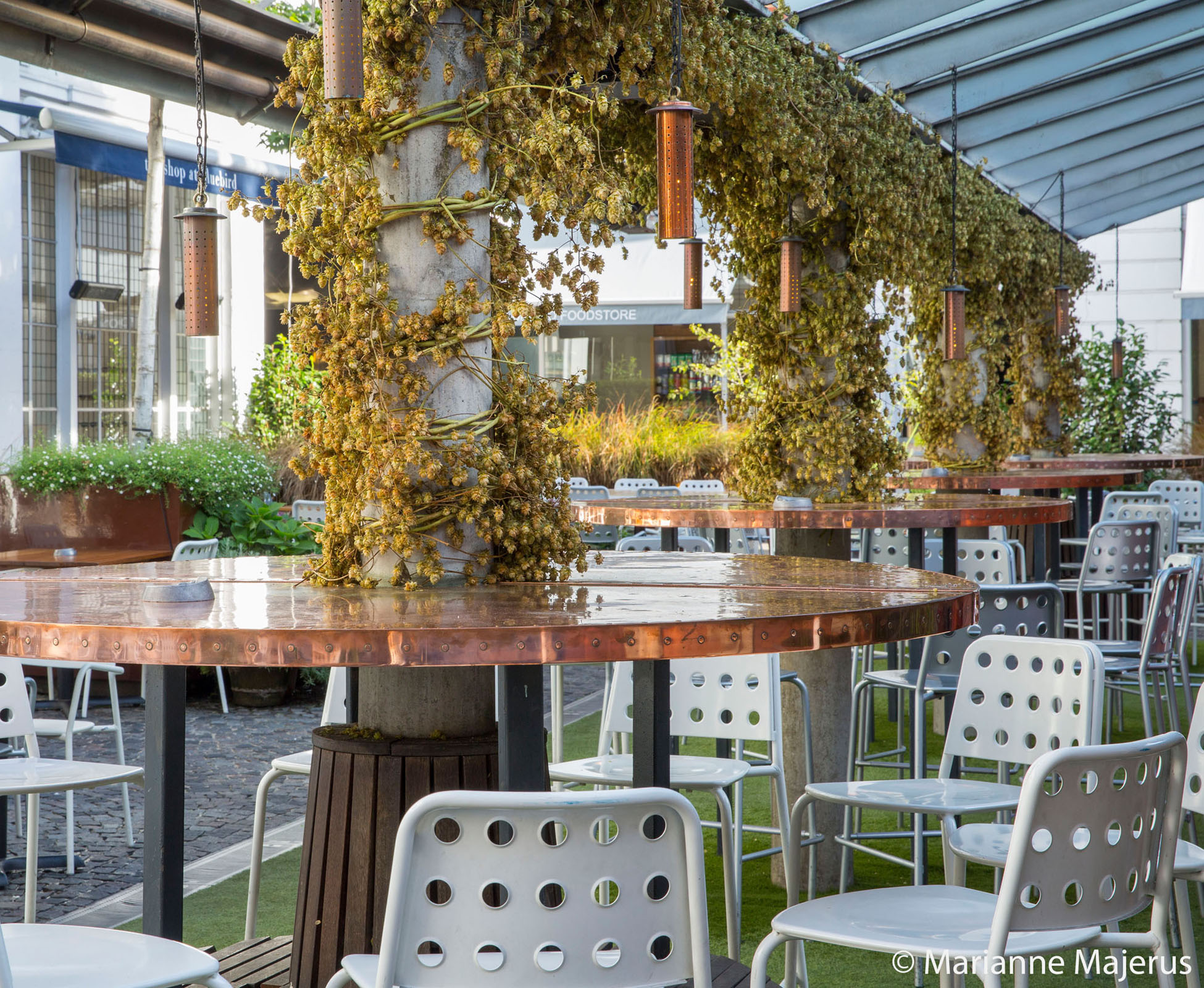 View of the covered pergola in Bluebird's courtyard with its new copper tables and hanging copper light, for a warm light atmosphere, night and day.
