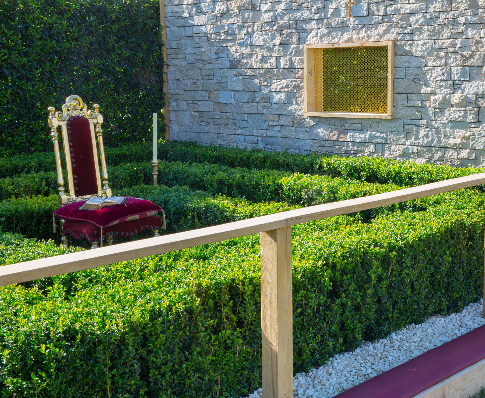 The red velvet chair in the controlled garden is surrounded by clipped evergreen box hedges.