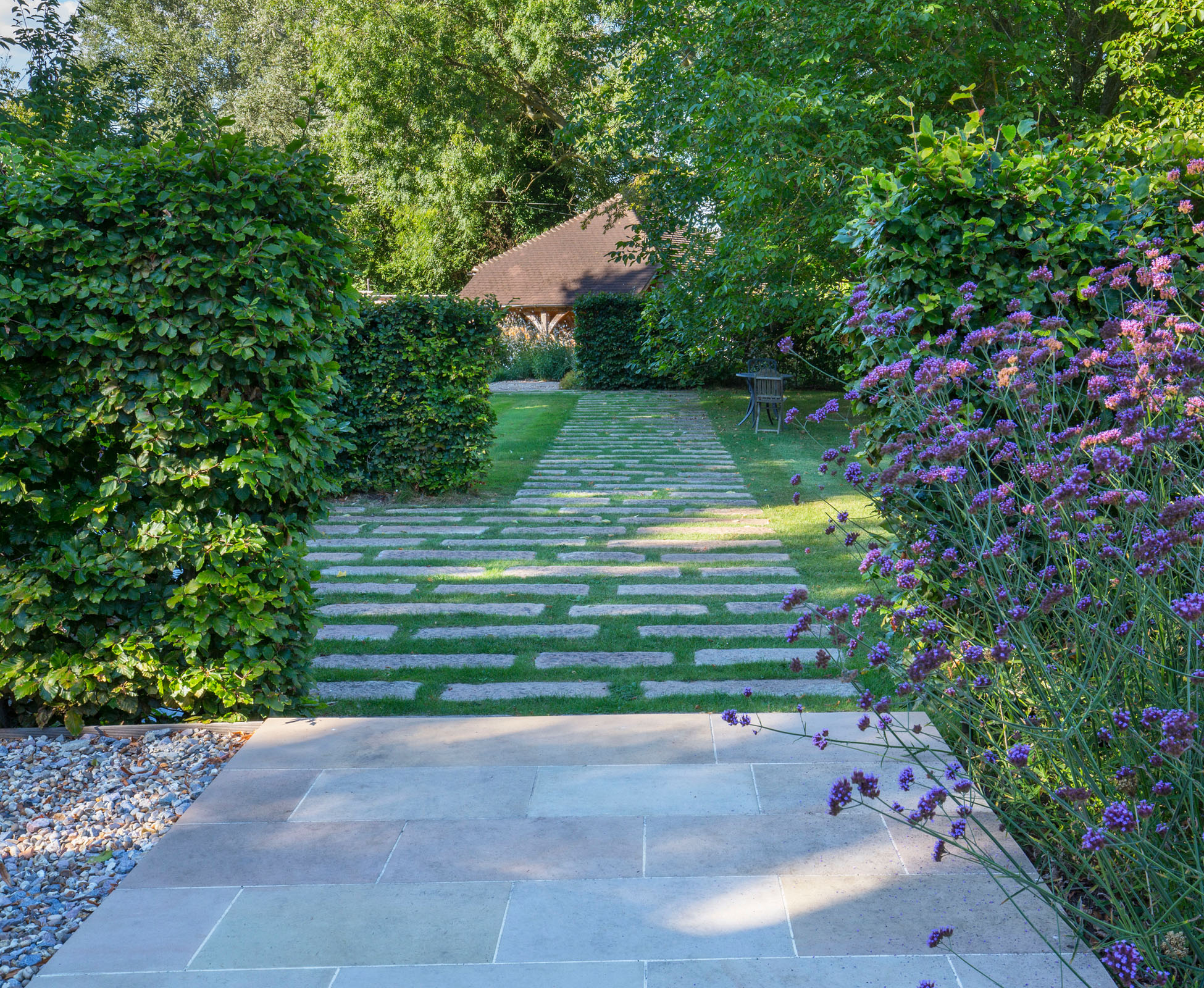 A step down from the hardwood deck onto the walking path leads to the lawn and the garage at the rear of this Richmond garden. The tall beech hedges break up the space, giving a rhythm to the planting.