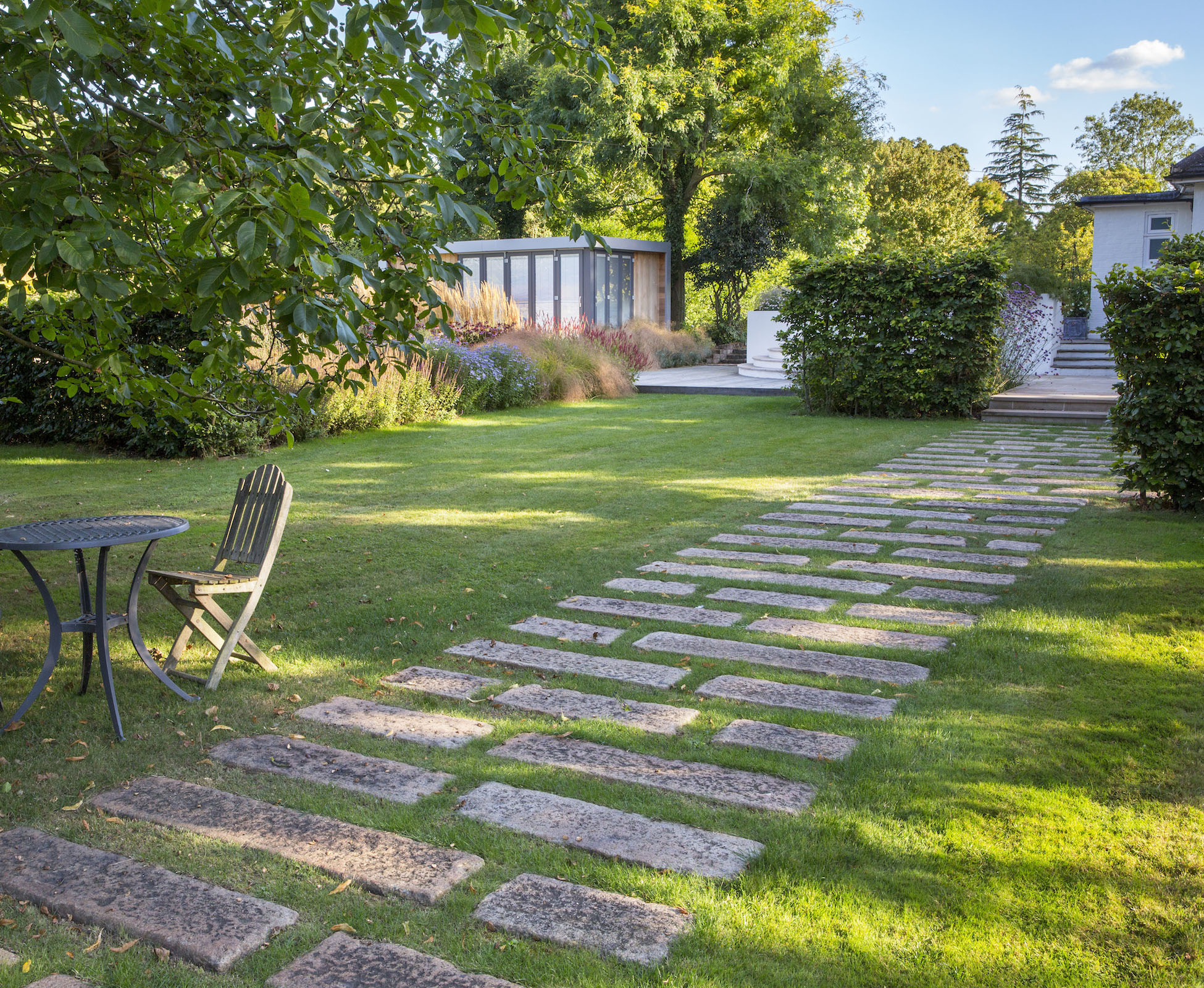 The dynamic path made of granite kerbstones takes you all the way to the hardwood deck, along some big herbaceous borders and tall beech hedges. A table and chairs are sitting on the lawn, under the old existing walnut tree.