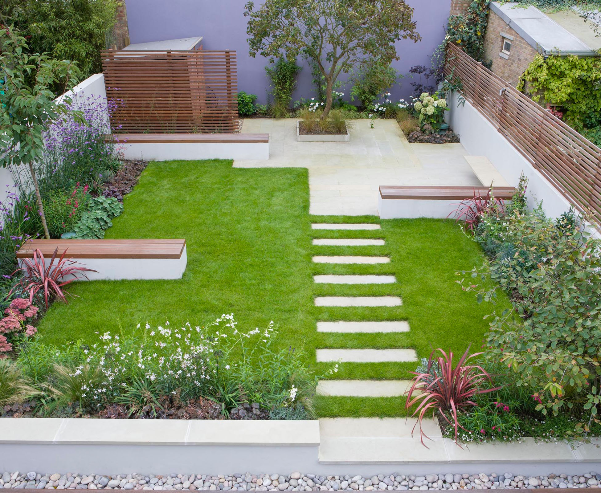 A wide view from the first floor of this house in Twickenham, South London, shows the whole garden with the lawn separating two seating areas and some staggered benches. The stepping stones through are the link tying in the whole design.